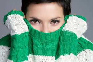 womancoveringmouthsweater